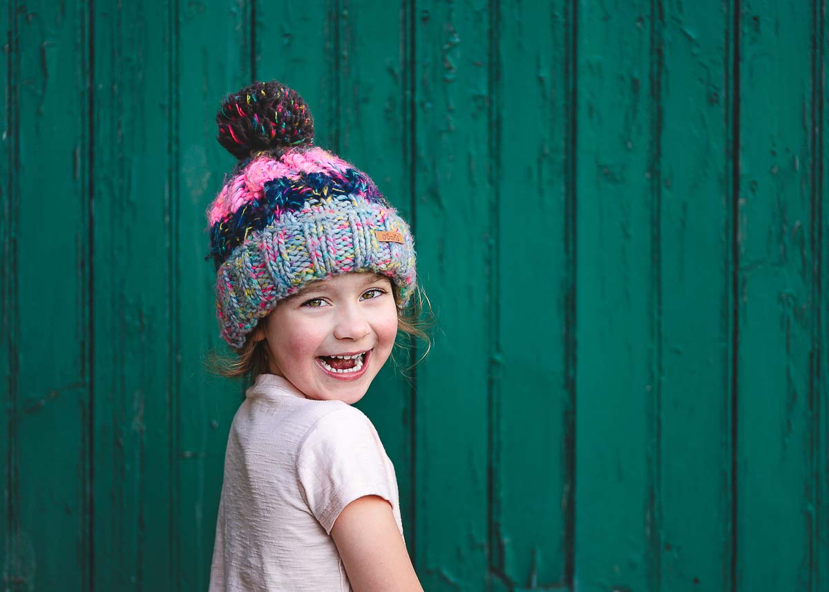 Little girl laughing during her photoshoot standing in front of a green wooden door in Edinburgh