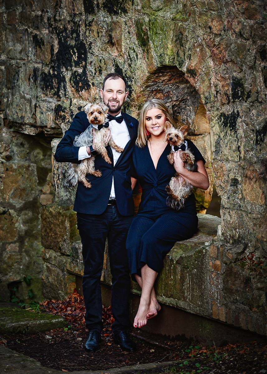 Husband and wife dressed to impress on their photoshoot with their two yorkshire terriers in Edinburgh