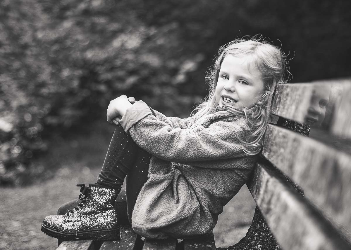Young girl sitting on a bench smiling for her family photoshoot sitting very relaxed with her foot on the bench