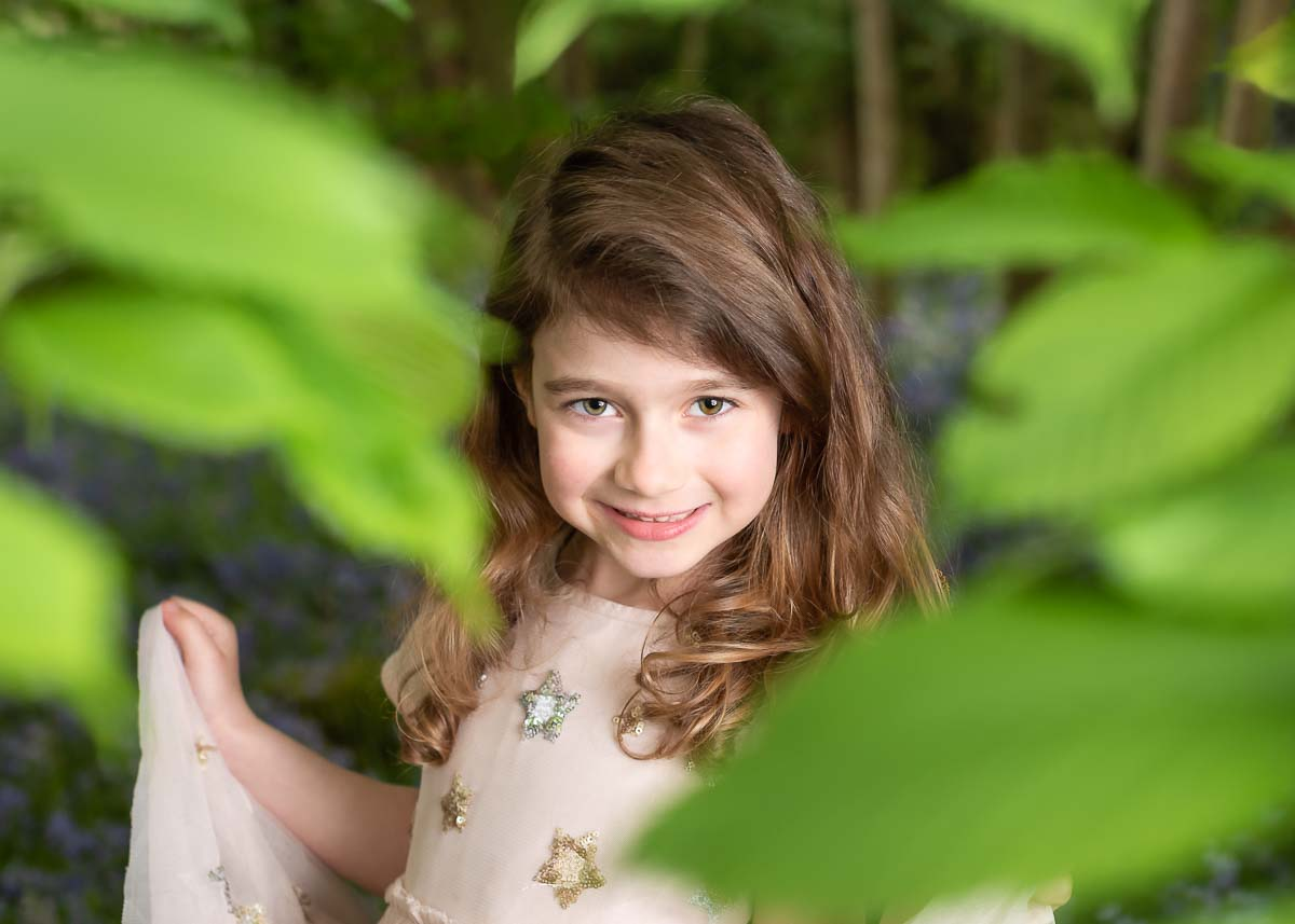 Little girl posing for her photoshoot in a field of bluebells framed with some tree leaves
