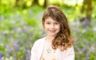 Little girl standing in a field of bluebells for her family photoshoot