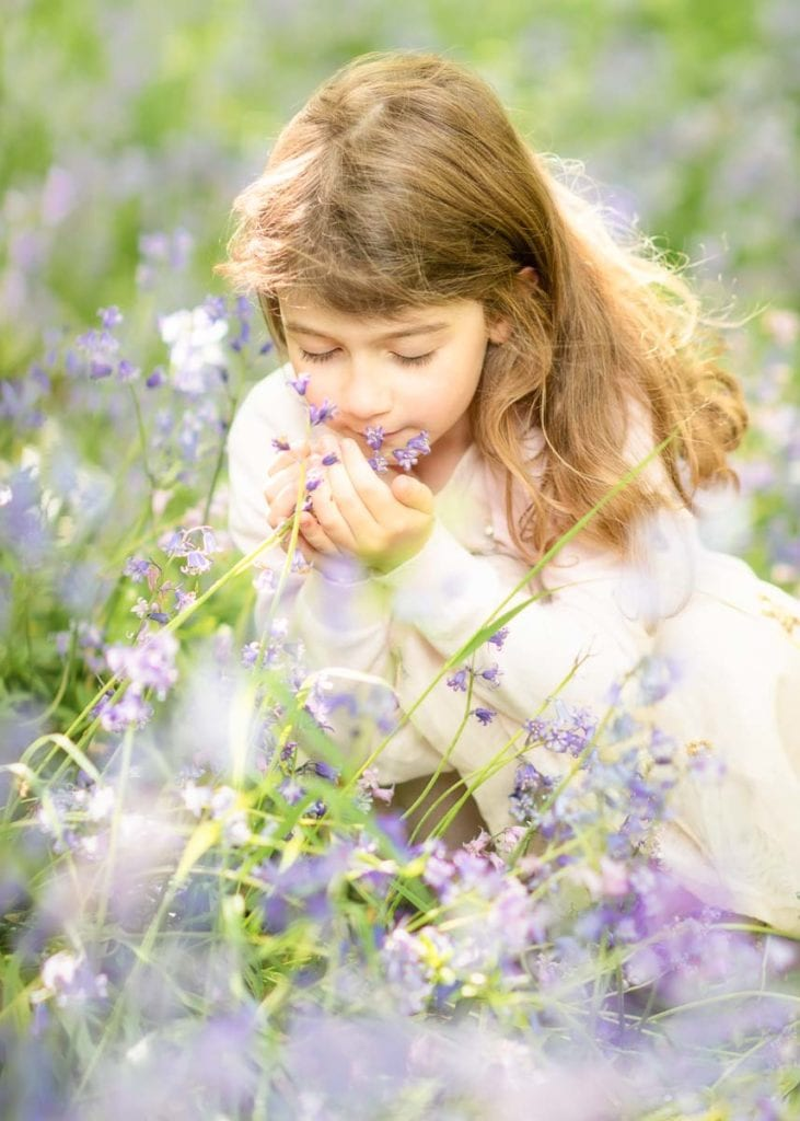 Little girl smelling bluebell flowers on her summer family photoshoot